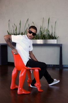 Pharrell Williams in what can only be described as the BEST.CHAIR.EVER.