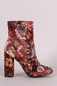 These booties feature a velvet fabrication with a multi colored floral print, wrapped round chunky heel, pieced design with top stitching, single sole, lightly