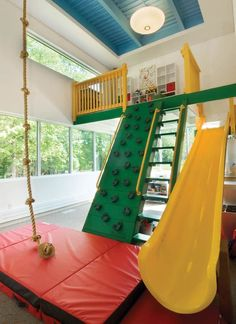the end of a hall in this home is a that includes an indoor jungle gym, rock climbing wall, rope swing and a door to the deck.At the end of a hall in this home is a that includes an indoor jungle gym, rock climbing wall, rope swing and a door to the deck. Indoor Jungle Gym, Kids Indoor Play Area, Kids Indoor Playground, Indoor Swing, Kids Gym, Kids Room Design, Playroom Design, Home Trends, Dream Rooms