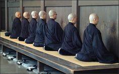 Zen monks sitting zazen on zafus on a tan.