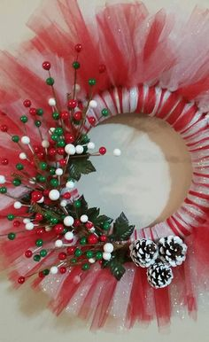 Decorate for Christmas! This red and white tulle wreath will decorate your door in style for Christmas. This wreath has three snow covered pine cones and red, white, and green berries. This wreath is 18 inches in circumstance and 3 1/2 inches in depth. Made in USA! Thank you