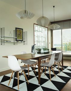 Dining room with IKEA geometric rug and pendant lights The dining table is from French retailer AM.PM., the pendants are by Him + Her, and the shelves are by Tomado Holland. An Ikea rug echoes the geometric motif found throughout the apartment.