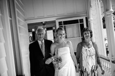 Bride walks with her mother and father to the ceremony for her wedding at Alberton House, Mt Albert, Auckland. Black and white. BeSo Studios create beguiling fine art family photographs for the walls of the most discerning clients homes. We specialise in wedding and family portrait photography, and supply prints on the highest quality media, framed in beautiful conservation standard frames. We are a high end studio located in the beautiful city of Auckland, New Zealand.