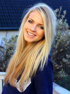 Fryzura na jesień: blond włosy dziewczyny są rozpuszczone . bluza granatowa z napisem . w tle jest: dom itp.