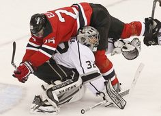Kings goaltender Jonathan Quick is flattened by Devils center Patrik Elias in the third period of Game 2 on Saturday night in Newark, N.J.