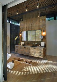 Tropical Master Bathroom with Freestanding Bathtub, frameless showerdoor, Wall sconce, Hardwood floors, European Cabinets
