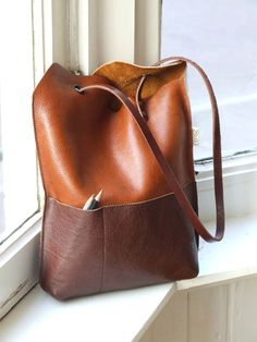 "Yin Yang bag:  ""I've made this bag before in canvas (view here)... The good thing is that the bag has two pockets now, a tiny one on the outside and a larger one on the inside. It's a very minimalist, yet practical design, because the bag closes automatically when you pick it up. ... I use reclaimed leather from a furniture maker nearby... And if you want to know more about working with eyelets: I wrote a blogpost about it today."""