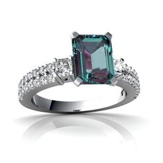 14K White Gold Emerald-Cut Alexandrite Engagement Ring - This is a stunning Emerald-Cut Alexandrite Engagement Ring. It features 34 diamonds that surround the elegant center gemstone. This ring also features two 2.5mm diamonds surrounding the center stone & 32 smaller diamonds around the band. The total gem weight for is 2.2 carats set in solid 14k White Gold. The band is 1/8 of an inch at its widest point down to 1/16 of an inch at the back & is 1/4 off the finger. #unusualengagementrings