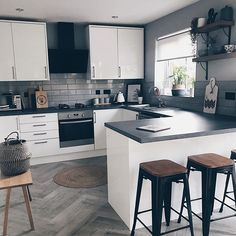 A monochrome kitchen with breakfast bar and industrial style bar stools.