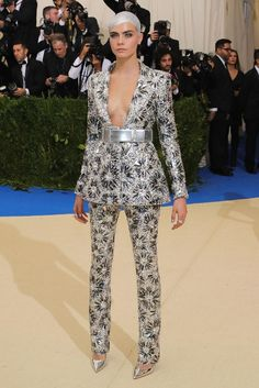 Model and actress Cara Delevingne teams her silver Chanel suit with her newly shaved head covered in silver. Picture / Getty.