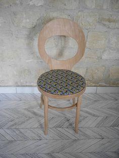 Description <><> Jolie chaise modèle Mouette de Baumann, entièrement poncée puis vernie. Et retapissée de tissu wax, pour lui donner un look plus tendance et actuel. La chaise était à lorigine blanc crème. Malgré tout le soin apporté, la couleur blanche se devine à certains endroits dans les nervures du bois. Elle comporte des irrégularités de bois ainsi que des taches au niveau des vis au dos.  <><> Style <><> Cette chaise vintage a un style original, mai...