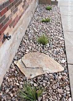Gravel around the foundation for drainage, plant shrubs along to help soak up water. Like the idea of the large rock to prevent erosion from the water spicket. Maybe a few cool pots or barrels with plants too? I like :)