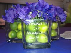 """These are centerpieces created entirely by my mom, @Bernadine Todd, for my grandma's birthday party! The glass square vases are from Dollar Tree and are laser engraved to say """"Bonnie's 70th Birthday Party"""" and the date of the party. Each vase was then filled with key limes and some artificial hydrangea flowers! These made great party favors for the guests, too!"""
