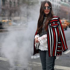 Draped and caped, the blogger Paola Alberdi pauses outside Tommy Hilfiger. - Fashion finery on the streets of New York City during New York Fashion Week.