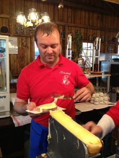 a man scrapes melted Swiss cheese for raclette