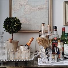 fabulous home bar styling by photographer Tara Sharma found on Laurel Home   love the boxwood topiary, crystal and touches of gold