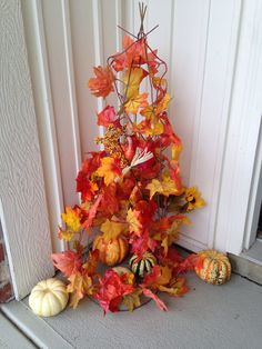 I used a tomato cage to wrap a long string of fall leaves around it and added smaller pumpkins to decorate it!