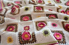 The roses that feature in this blanket are seriously textured, with two separate layers of petals. They are set in a two-colour openwork frame and complemented by simple starburst squares. A deep, striped border, with a crimped edge completes the blanket.