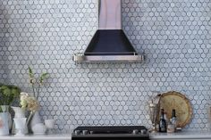 Amazing kitchen features a black and silver range hood lining a marble hex tiled backsplash over a black stove.