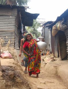 Woman carrying water through a neighborhood by waterdotorg, via Flickr