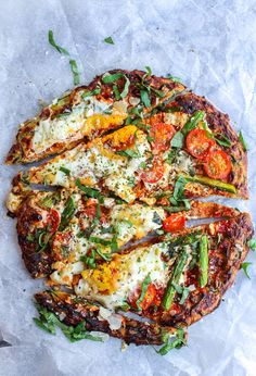 Zucchini Crust Breakfast Pizza topped with sliced asparagus, cherry tomatoes, eggs, and a sprinkling of parmesan cheese. Grain Free option too!