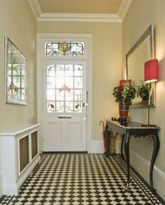 stained glass details on a white door, cream walls with white plaster details, black and white mosaic floor, hallway decorating ideas, black vintage table, with a flower vase and a lamp, near a mirror