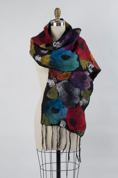 Eileen Scarf by Elizabeth Rubidge . A lush garden of abstract flowers adorns this scarf, all created from pieces of hand-dyed silk felted onto a base of soft, warm wool. Curly locks of wool fiber are interspersed throughout, adding playful texture.