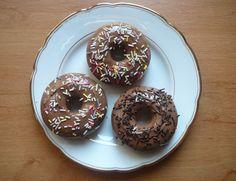 Nadýchané domácí donuty bez smažení, krok 5: Donuty vyndejte s formy a dejte na rošt. Jakmile úplně vychladnou, rozehřejte nad parou nebo v mikrovlnce čokoládu a namáčejte do ní do poloviny donuty. Posypte libovolným zdobením.
