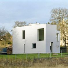This white rectangular box with an array of windows on three sides is a family retreat located in the mountains in Pernink, Czech Republic