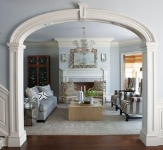 The dining and living rooms are set in a formal arrangement, each with a fireplace centered on the elliptical arches from the entry hall. Designed by @dvharchitects