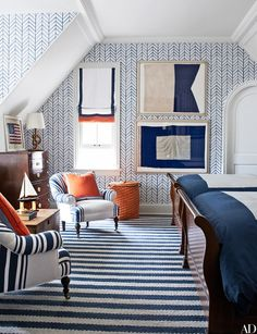 A graphic Serena & Lily wallpaper enlivens the boys' room; chairs upholstered in a denim stripe by Ralph Lauren Home flank an 1870 English chest, the framed naval flags are vintage, and the rug is by Montagne Handwoven.