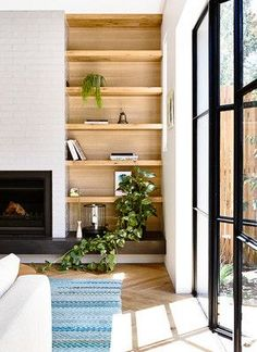 """While most built-in shelves tend to skew towards the camouflage effect, we love the idea of mixing and matching materials against contrasting backdrops. Take some cues from this contemporary space and stick to a """"less is more"""" approach to really highlight the wooden build of the shelves."""