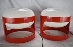 Pair of Joe Colombo table lamps from 1960s Joe Colombo. Two 'KD27' red table lights, 1960s cult objects! Made by Kartell, Noviglio. There is a crack in the bottom of one lamp, see picture 3 European 2 pin plug.  Dimensions H. 22.5 cm, D. 25 cm