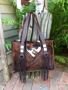 A tricolor cowhide Buckaroo Diaper Tote with suede lined side pockets, the owners initial on the flap in tan suede with a turquoise stone, and hand cut fringe. This one went to California. gowestdesigns.us
