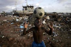 """From the Reuters """"The beautiful game"""" slideshow: An Angolan youth plays soccer in the streets of the capital Luanda, January 30, 2010. REUTERS/Rafael Marchante"""