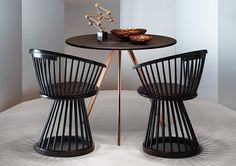 Dining chair with a pedestal base and back composed of oak spindles; with an upholstered seat. Fan Chair from the Fan Collection by British designer Tom Dixon for his eponymous brand. A contemporary reinterpretation of the traditional British Windsor Chair. Here shown in black stained oak. Also available in natural oak.