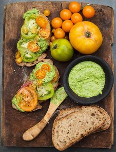 A wooden board with pieces of brown bread topped with large slices of tomato and green pesto, a bowl of pesto and tomatoes