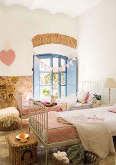Dormitorio infantil con dos camas, baúles de fibras y paredes mitad lisas mitad de piedra_00317259