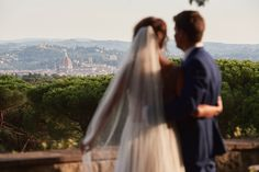 Newlywed bride and groom looking over at the stunning views of Florence, Italy.