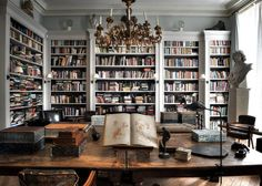 Shelf upon shelf of books, have you ever seen a more scholarly library? This office space features a large wood desk w/ classic artwork & a gold candelabra chandelier.