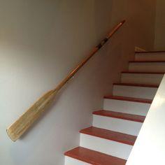 Vintage wooden oar repurposed as stair hand rail