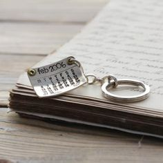 A custom-made, hand-stamped silver calendar keyring, with your special date marked with a Swarovski Crystal or a circle. Whether it is a birthday, graduation, engagement, birth of a baby, anniversary, wedding, or any important date past, present or future, the special date is accented with either a circle, just as you would see on a paper calendar, or a white Swarovski Crystal.