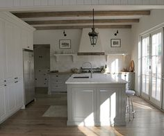 White and gray kitchen features rustic wood beams on ceiling accented with a glass and iron ...