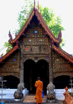 Buddhist monk entering rustic wooden temple, Northern Thailand