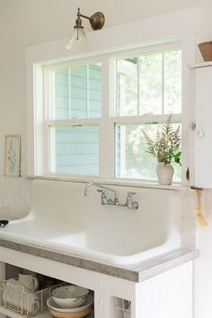 white-farmhouse-sink-concrete-countertops-budget-kitchen-remodel farmhouse sink Kitchen of the Week: In Montana, Rustic Chic on a Budget - Remodelista White Farmhouse Sink, Farmhouse Sink Kitchen, Old Kitchen, Modern Farmhouse Kitchens, Kitchen Island, Farmhouse Style, Kitchen White, Vintage Farmhouse Sink, 1970s Kitchen