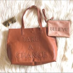 "Tote and pouch Tote and pouch. ""Take a chance"" is sewn onto the tote and ""believe"" is sewn into the pouch that comes with it. Both are vegan leather. The outside of the pouch matches the color of the inside of the tote. Really good condition. Never got used! Super cute little set! 15L x 13H x 5W Bags Totes"