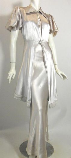 30s gown of silver satin with long peplum overjacket. Deco seaming on lapel and aqua trimmed hem of jacket, netting supports puff sleeves.