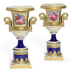 A PAIR OF CHAMBERLAIN'S WORCESTER BLUE-GROUND URN-SHAPED PEDESTAL VASES  CIRCA 1825-35, IRON-RED SCRIPT MARKS  Each of slender form, with gilt dolphin handles, below white beading to the upper rim, painted with a panel of flowers on a yellow ground within a gilt cartouche, the lower part with radiating gilt lappets on a spreading blue stem and cylindrical blue and gilt pedestal and square base gilt with anthemion, slight rubbing to gilding  9¾ in. (24.7 cm.) high (2)