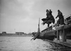 """""""Plunging Policemen"""". Three fully-clothed members of the Port of London Authority Police jump into the West India Docks during the annual test of their life jackets. (Photo by R Wesley/Getty Images)."""