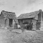 The owners of this cabin appear in front of their home in Union Point, Greene County, GA, ca. 1900. The timber for such cabins was usually cut and hewn on the building site. - Courtesy of Georgia Archives, Vanishing Georgia Collection